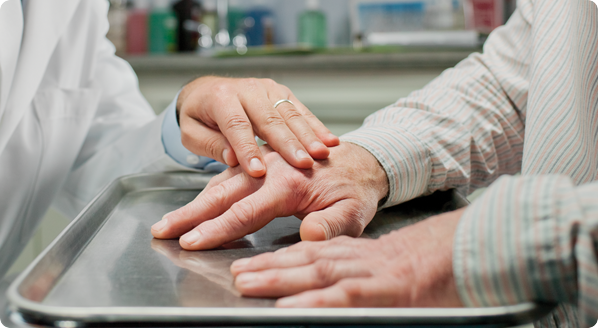 Closeup of healthcare provider and patient's hands, flat on an exam tray